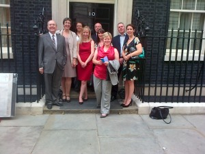 Employees from Clarke Willmott and Jessie May Trust in front of No.10 Downing Street door
