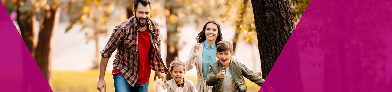 Smiling family running together through the woods