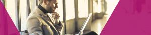 Man sat down looking at a laptop