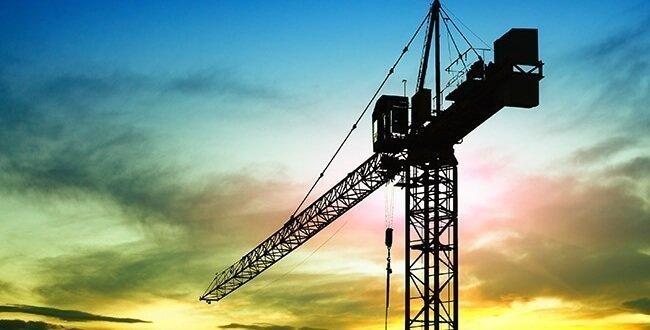 A large crane graces a city skyline at dusk