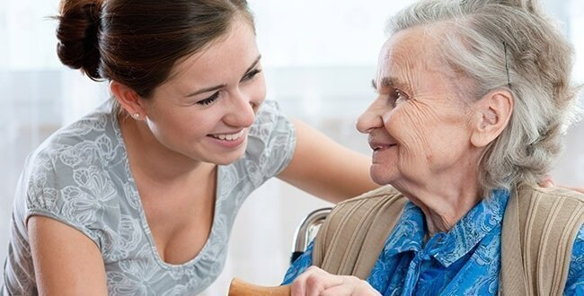 A smiling carer chats with an elderly lady