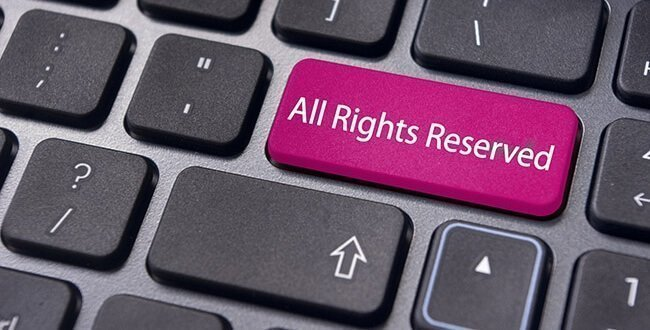"Keyboard with one key coloured pink and labelled ""All rights reserved"" - Intellectual property lawyers"