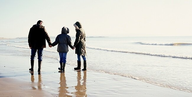 A mum, dad and child hold hands as they walk along a beach