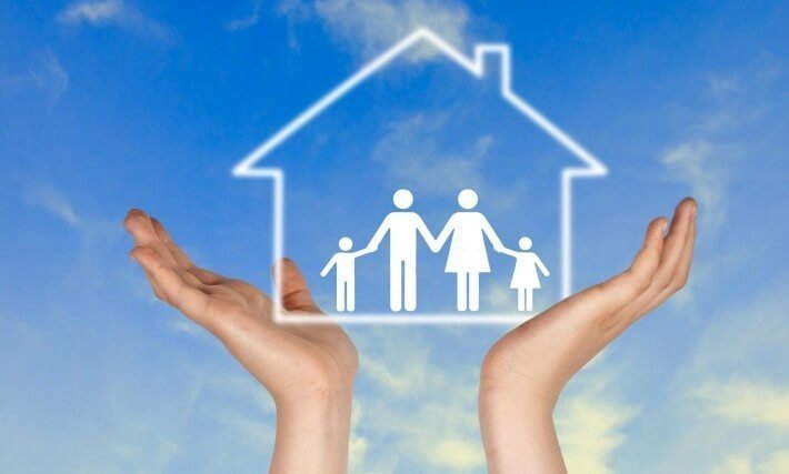 A person holds the silhouette of a family house in their hands