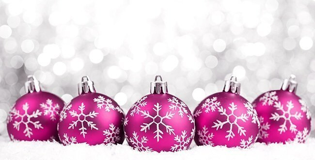 Pink Christmas baubles in snow