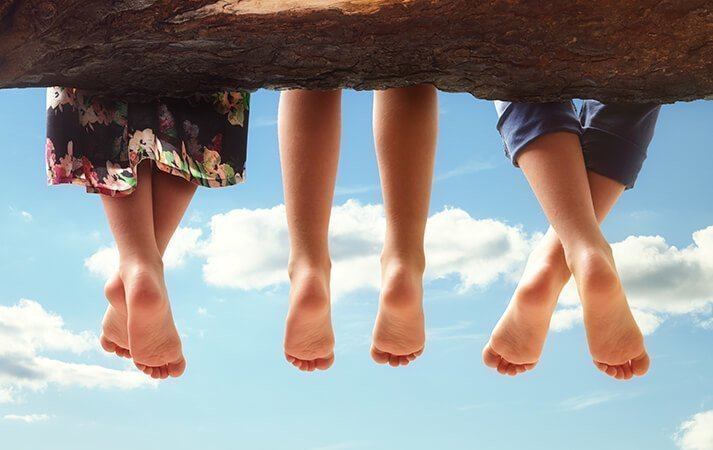Three children sit barefooted on a tree branch