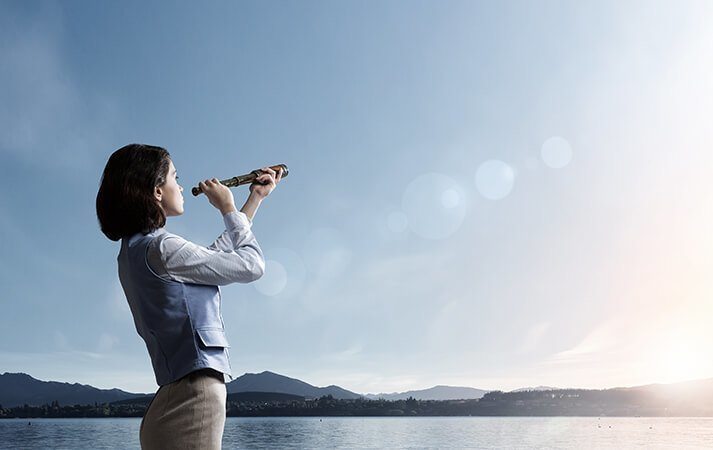 Woman looking at the horizon through a spyglass
