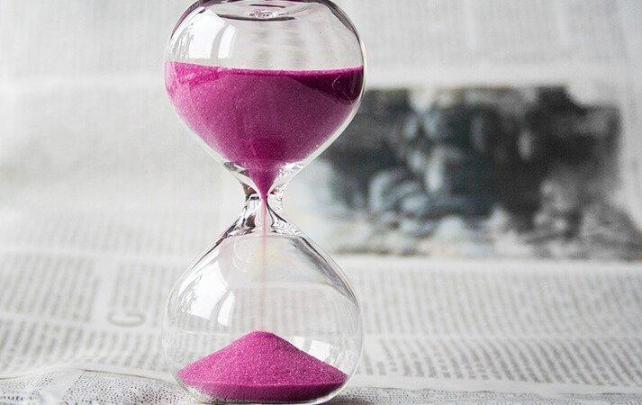 Hourglass stood on newspaper