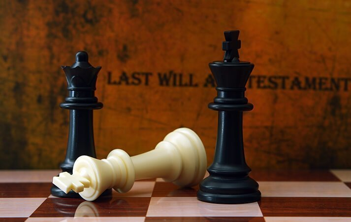 """Chess pieces in front of a wall that reads """"Last will and testament"""""""