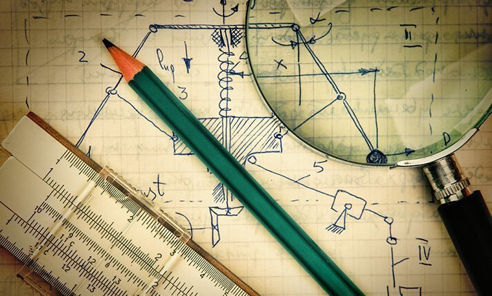 Pencil, ruler, and magnifying glass on top of a hand drawn schematic