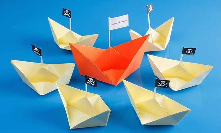 Paper boats - the center boat flying a flag that read 'Intellectual Property' surround by six boats flying pirate flags