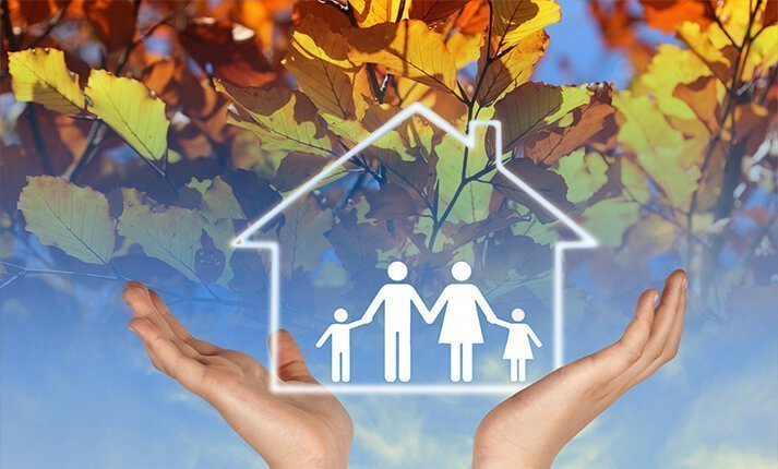 Hands holding the image of a house & family against the backdrop of a blue sky that fades into Autumn leaves