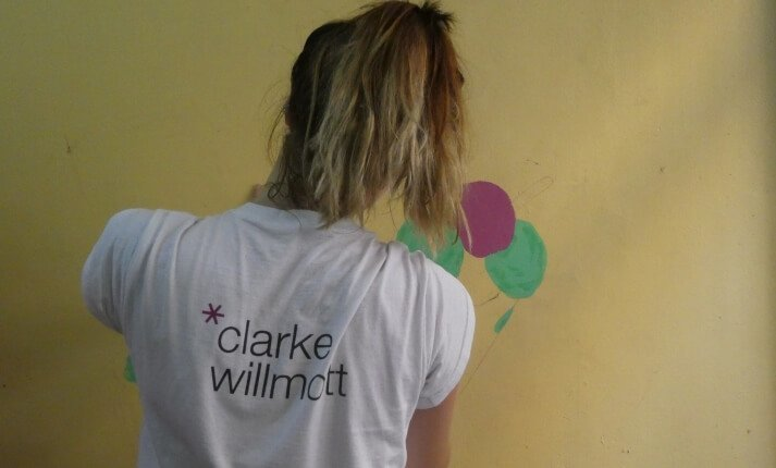 Georgia Harding helping paint a picture on the wall for elped at CanKids in India