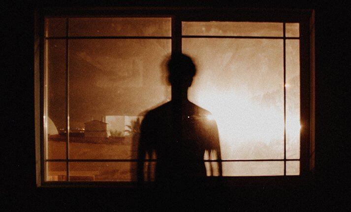 Silhouette of a person stood by a window