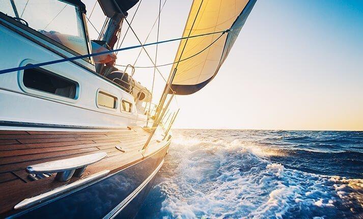 Yacht sailing towards the sun