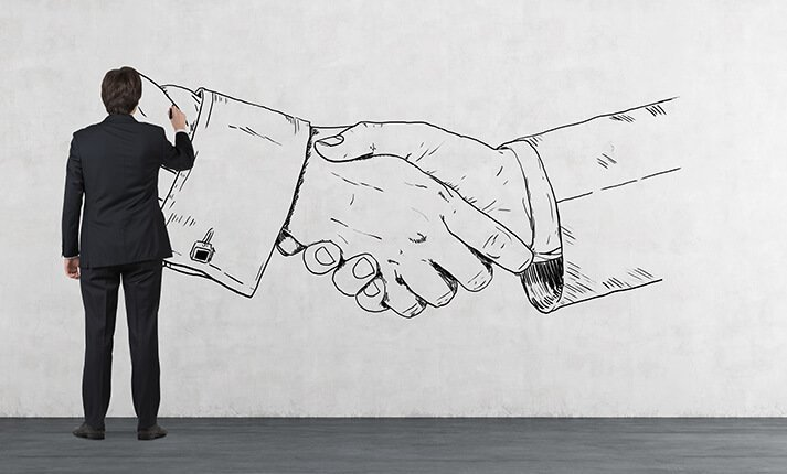 Businessperson creating a mural of a handshake