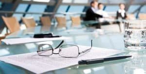 Glasses and paperwork on table with Corporate and M&A executives in the background