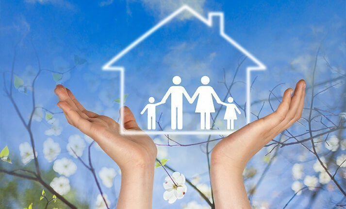 Hands holding aloft the outline of a family inside a house against a backdrop of blue sky and spring flowers