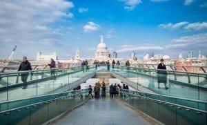 People walking across a bridge in London