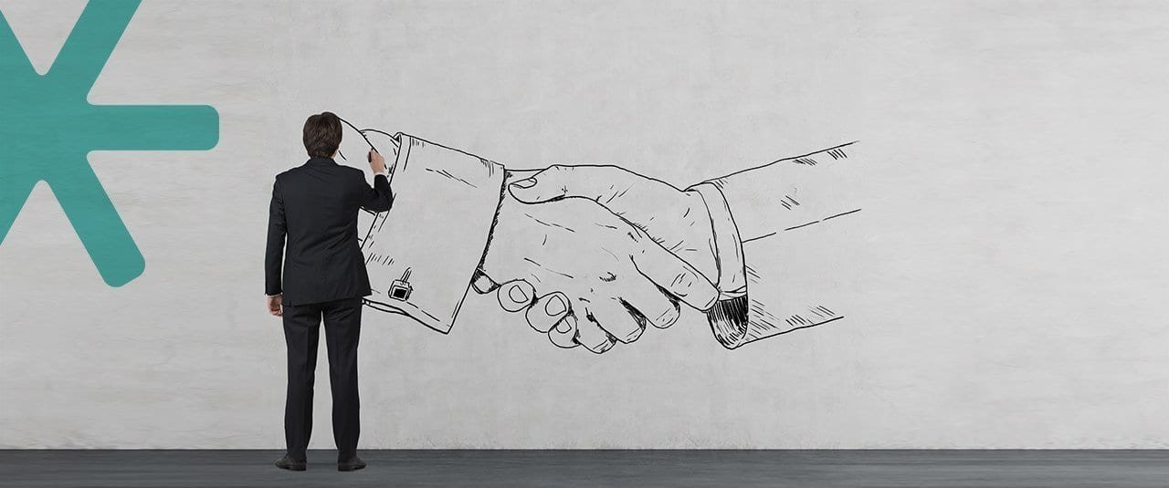 Business person drawing a handshake on a wall