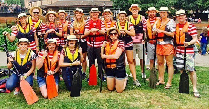 """""""The Clarke Willmott Gondoliers"""" Dragon Boat race team stood with their paddles by the river bank"""
