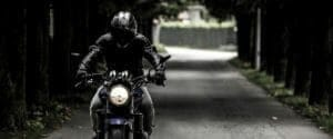 Motor cycle rider driving down the road