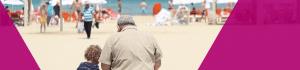 Grandad at kid sat on the beach