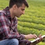 Modern farmer using a tablet in a field