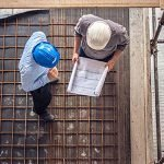 Multiple builders looking at a building plan and walking up and down scaffolding